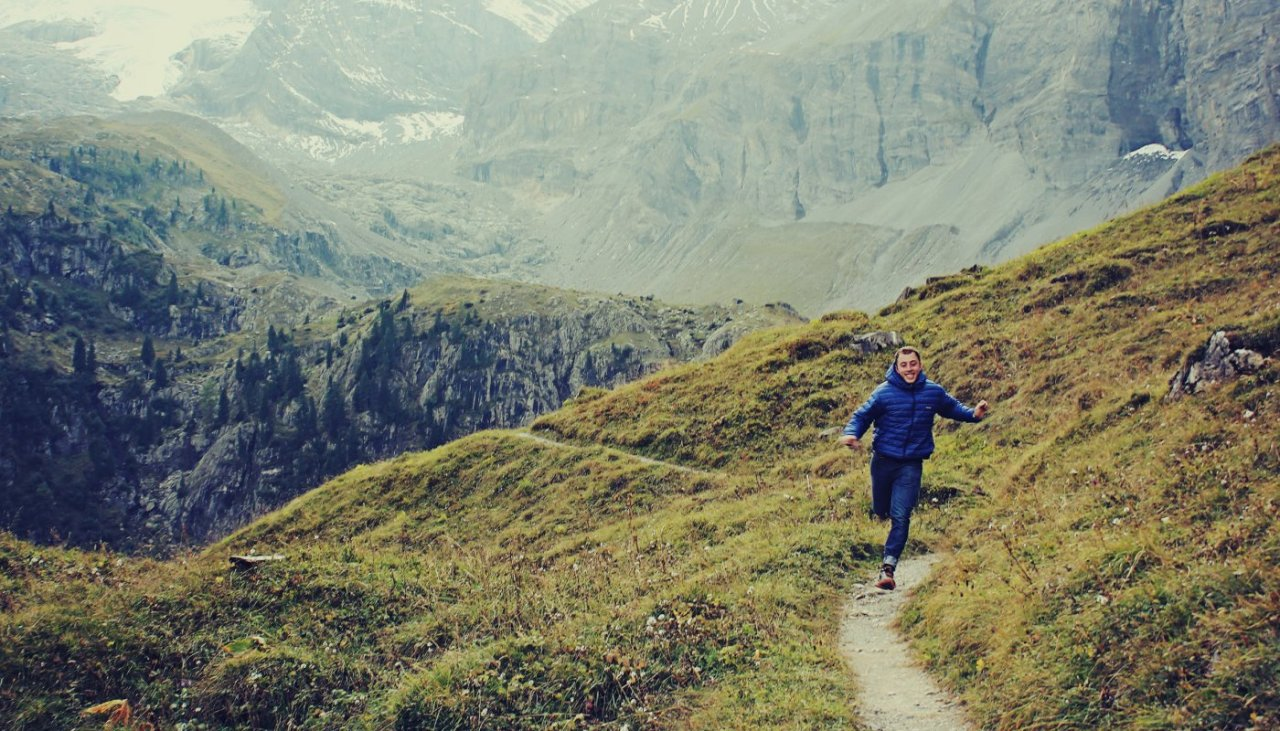 Happy man running on a mountain trail