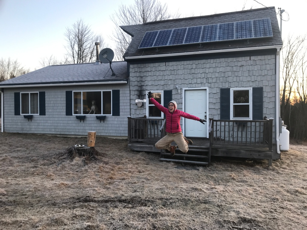 me jumping for joy in front of our new home, a small grey cottage with solar panels. my dog is looking through the window